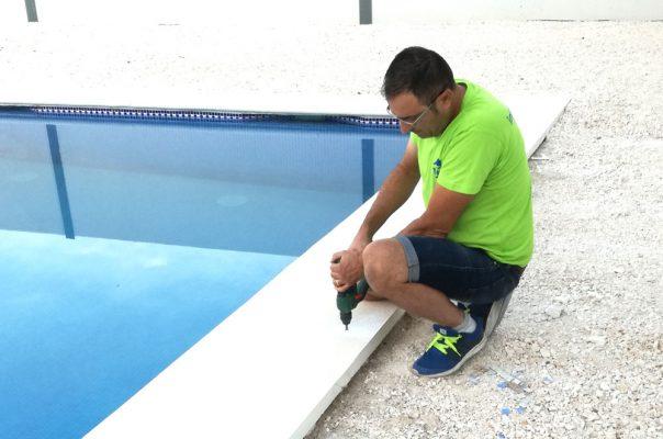 Juan Gálvez instalando instalando un cobertor de piscina